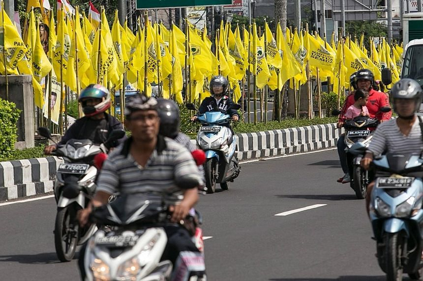 Motorcyclists riding past large flags of the Golkar party, which officially started its national congress in Bali yesterday. The meeting of Indonesia's second- biggest party in Parliament was opened by President Joko Widodo. Eight leaders are contest