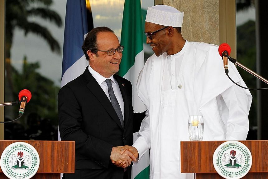 French President Hollande (left) with Nigerian President Buhari at a joint news conference in Abuja, Nigeria, yesterday. They held talks at the presidential villa before regional leaders met to discuss the terrorist conflict.