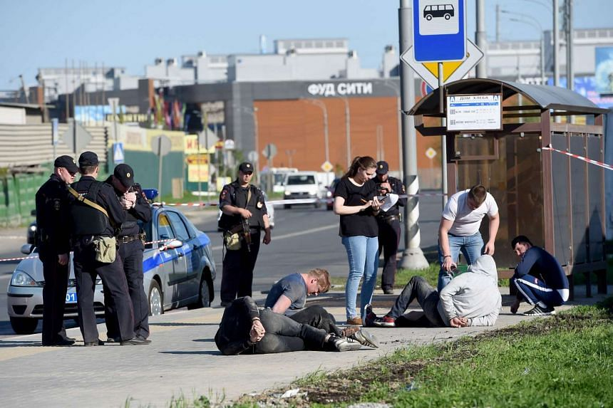 Police officers interrogate suspects next to a cemetery in south-west Moscow on May 14, 2016.