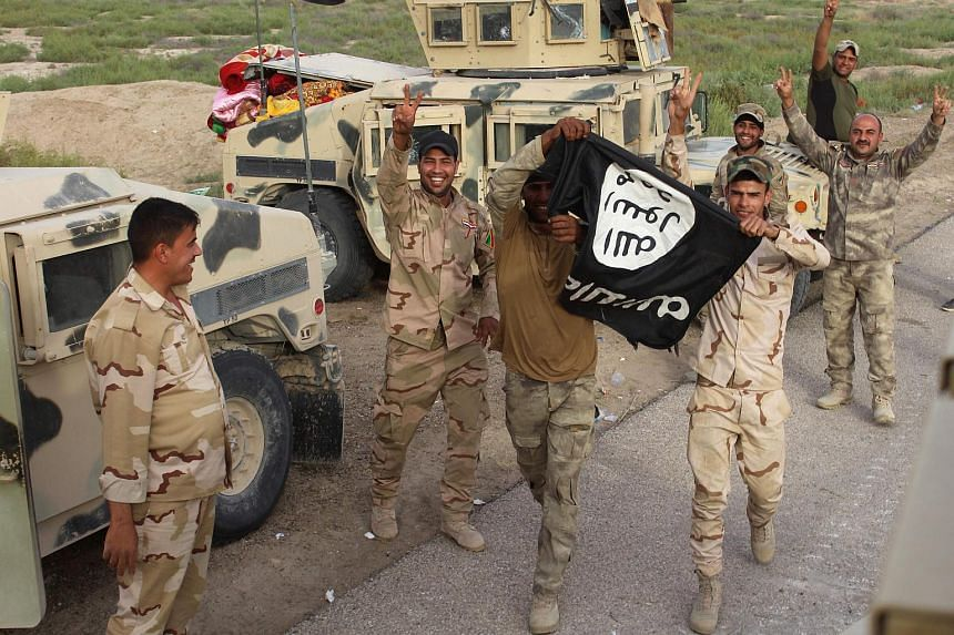 Fighters from the Iraqi pro-government forces hold up an Islamic State (IS) group flag.