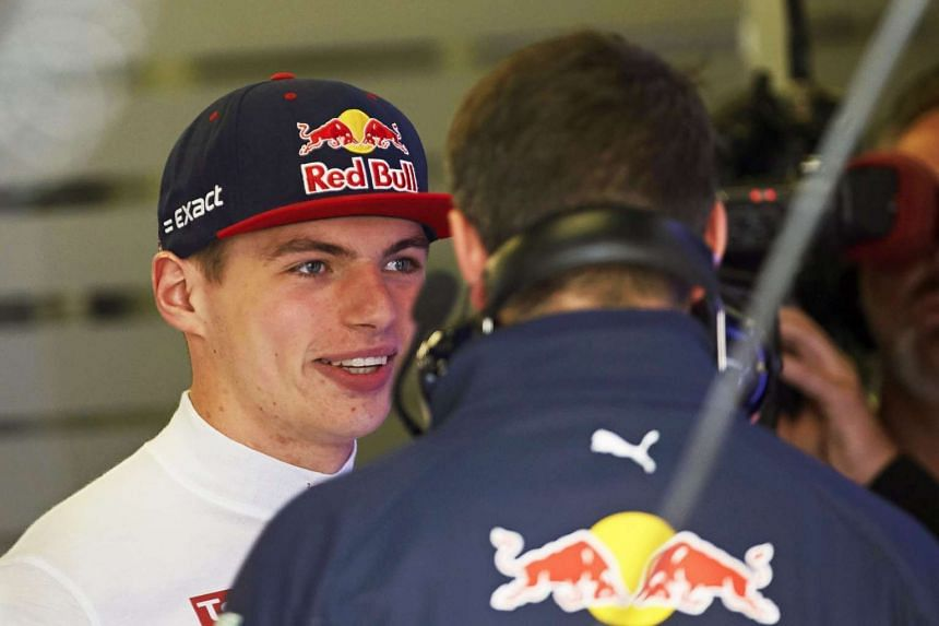 Verstappen (left) talks with a mechanic during the third training session in Spain.