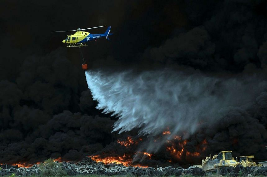 A helicopter dropping water over tyres burning in an uncontrolled dump near the town of Sesena, on May 13, 2016.