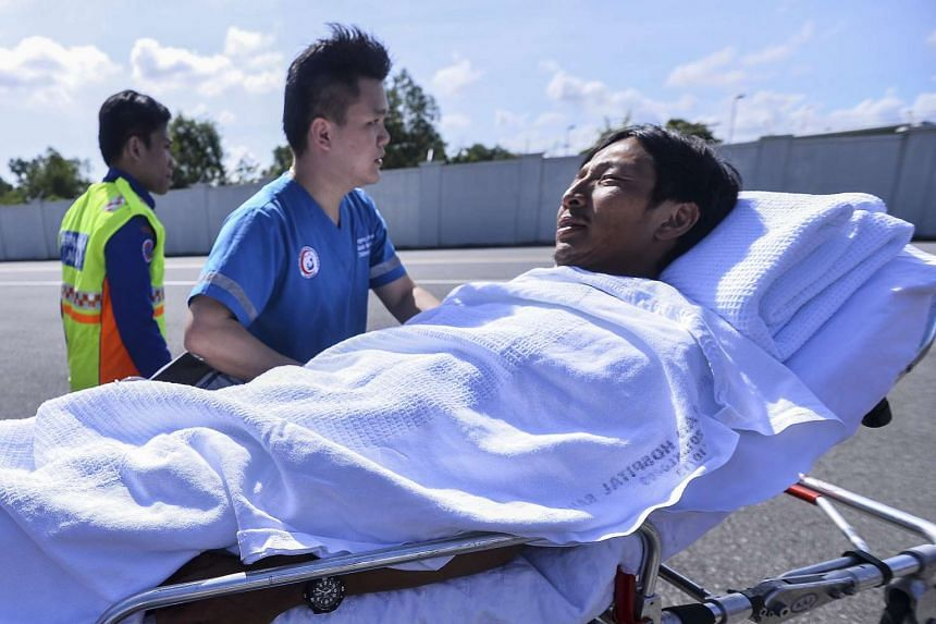 Tommy Lam Wai Yin is transported away on a stretcher at Kota Kinabalu International Airport, on May 13, 2016.