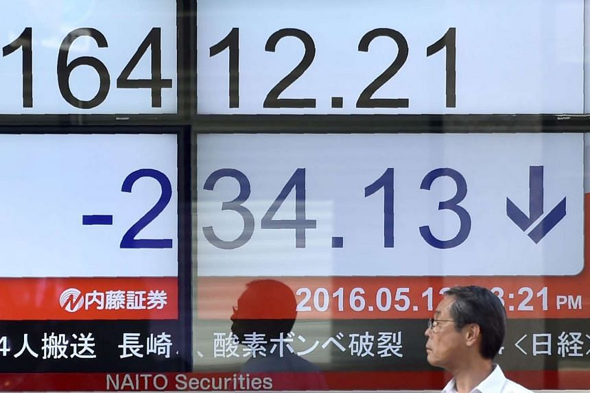 A pedestrian stands in front of a quotation board flashing the Nikkei key index from the Tokyo Stock Exchange, on May 13, 2016.