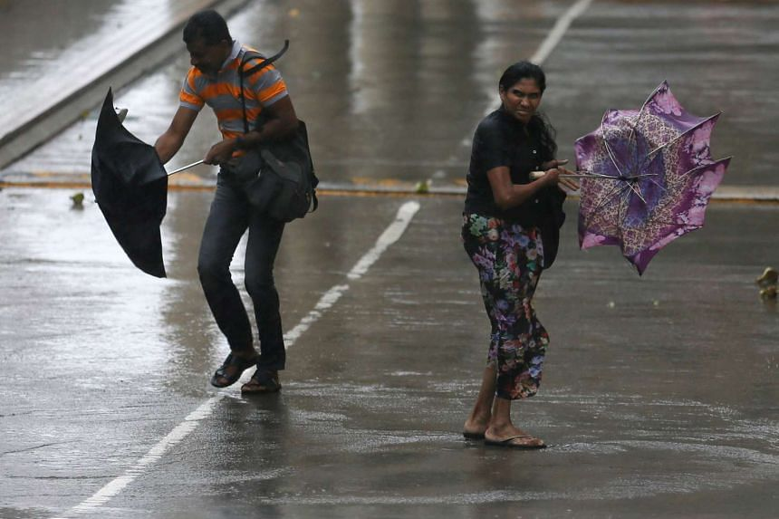 A man and a woman struggle to hold their umbrellas from high wind and rain during a wet day in Colombo, Sri Lanka, on May 15, 2016.