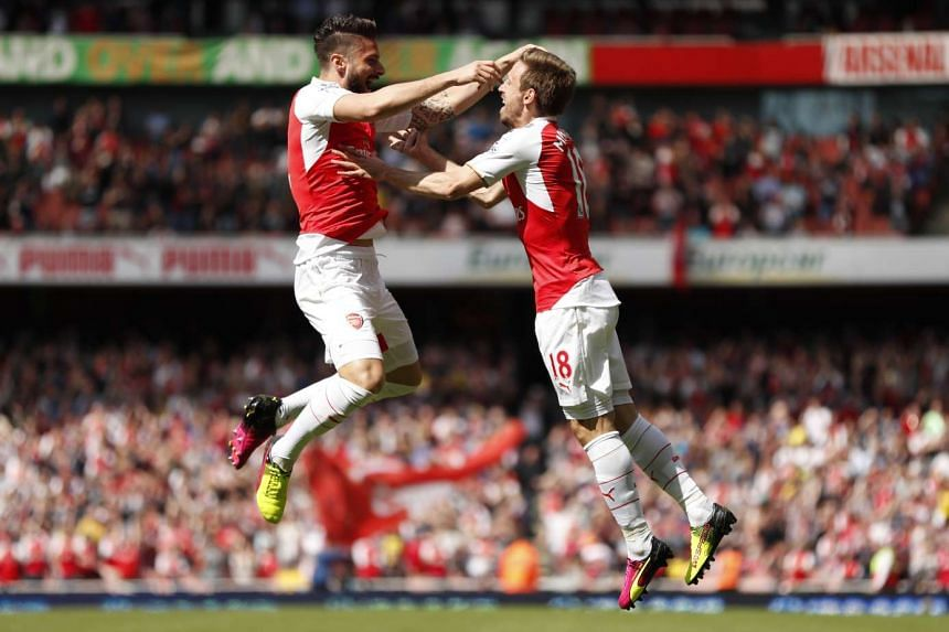 Olivier Giroud celebrates with Nacho Monreal after scoring the first goal for Arsenal in the Barclays Premier League at Emirates Stadium on May 15, 2016.