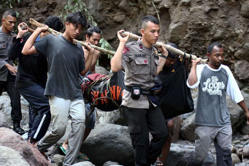 Indonesian police and villagers carry the body of a flash flood victim in Sibolangit, North Sumatra, on May 16, 2016.