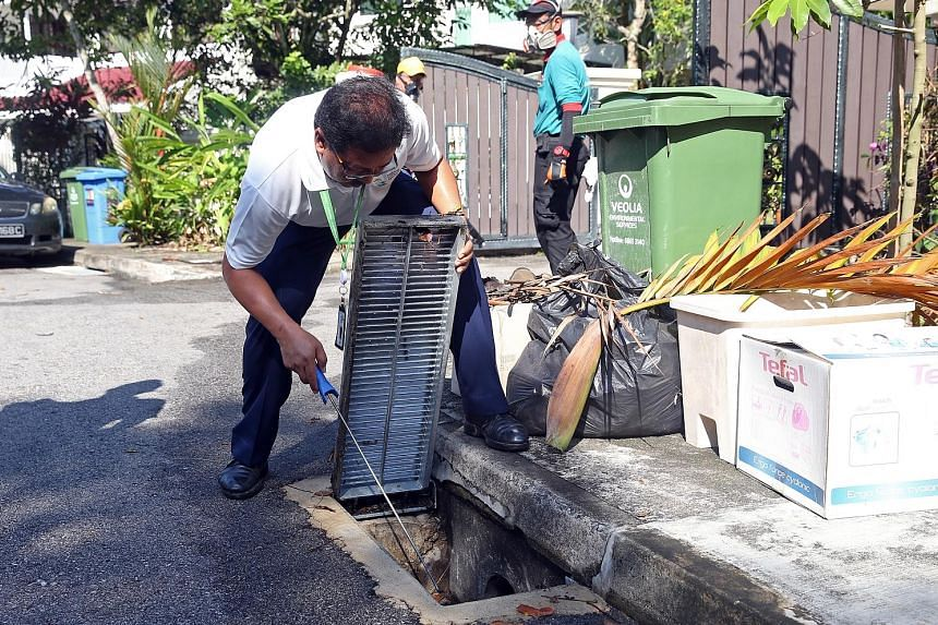 NEA officers and contractors preparing to carry out misting and inspection operations in Watten Estate yesterday morning. Dr Khor said both Zika and dengue viruses are spread by the Aedes aegypti mosquito and residents must remain vigilant. (Below) A