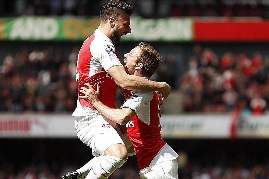Olivier Giroud (left) celebrating with Nacho Monreal after scoring Arsenal's first goal. The Frenchman enjoyed a hat-trick in the 4-0 win, which maintained Arsene Wenger's record of always finishing above Spurs in the league.