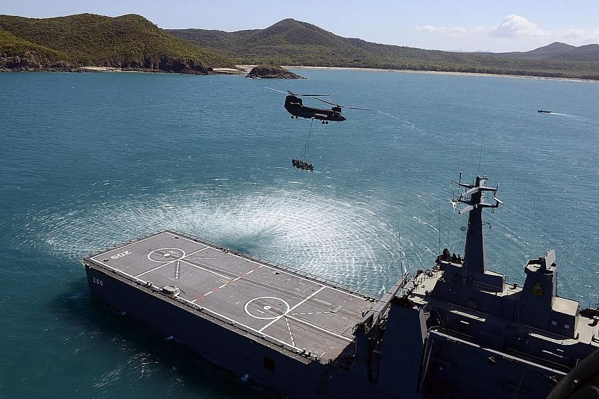 (Above) Troops from the Singapore Armed Forces and the Australian Defence Force during a preview of Exercise Trident at Freshwater Bay in Rockhampton, Queensland. (Below) Another scene from Exercise Trident.