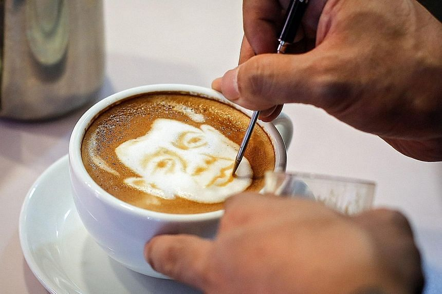 Filipino graphic artist and barista Zach Yonzon draws the face of Philippine President-elect Rodrigo Duterte on a cafe latte called Latte Duterte inside his cafe and cake studio in Quezon city, north-east of Manila.