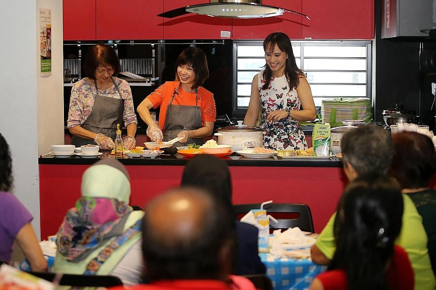 Dr Khor (centre) giving a cooking demonstration of two dishes featured in the recipe book - sweet potato oats and chicken and vegetable stew - at the launch event yesterday.