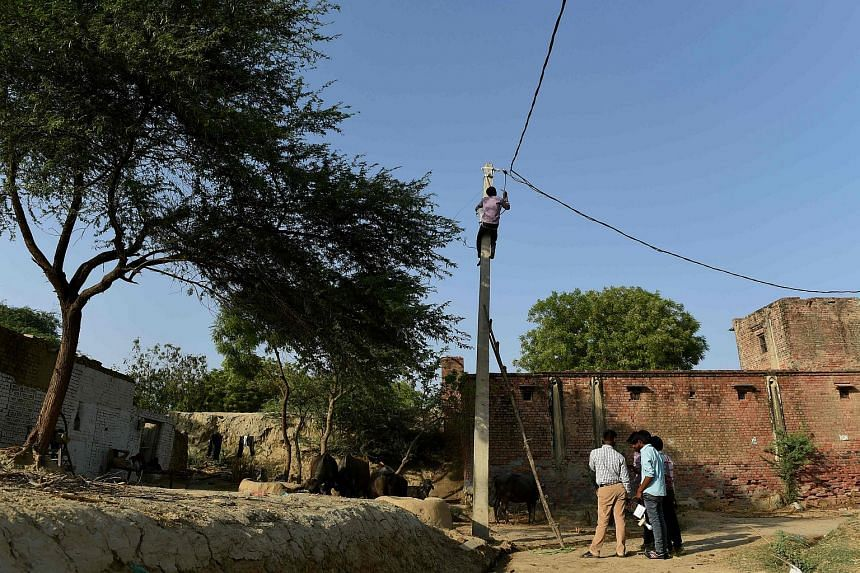 An Indian worker climbs up an electricity pole as others look on during the process of electrification in the village of Anandpur.
