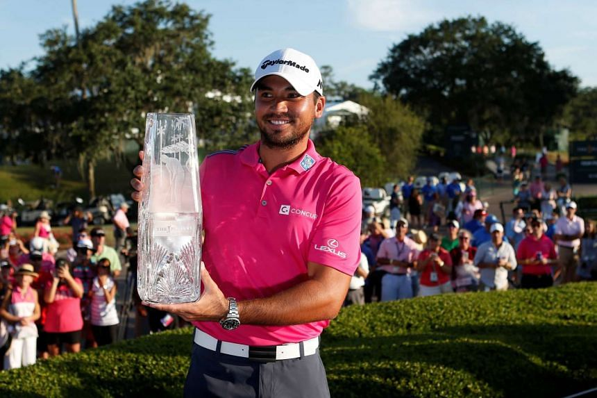 Jason Day holds the championship trophy after winning the 2016 Players Championship golf tournament.