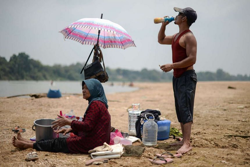 A man (right) drinks water along the dry banks of the Pahang river.