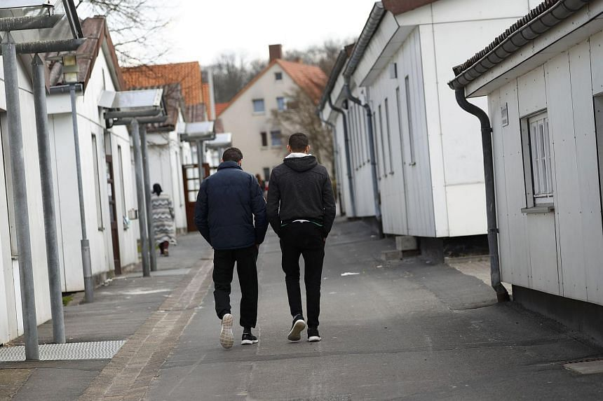Migrants strolling between barracks at the camp for refugees in Friedland, Germany, on April 4, 2016.