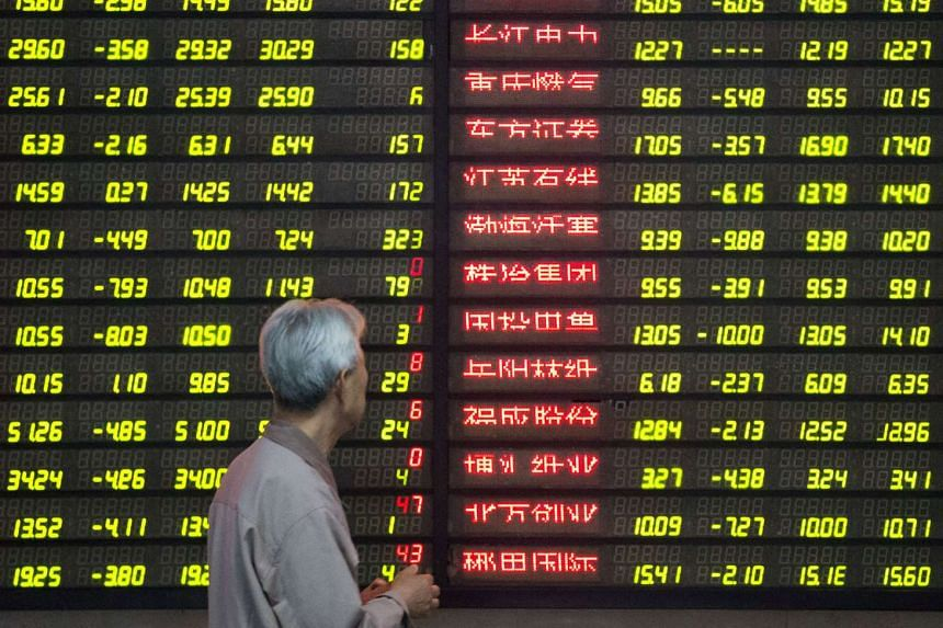 A man looking at an electronic screen showing stock information at a brokerage house in Nanjing, Jiangsu Province, China, on May 9, 2016.