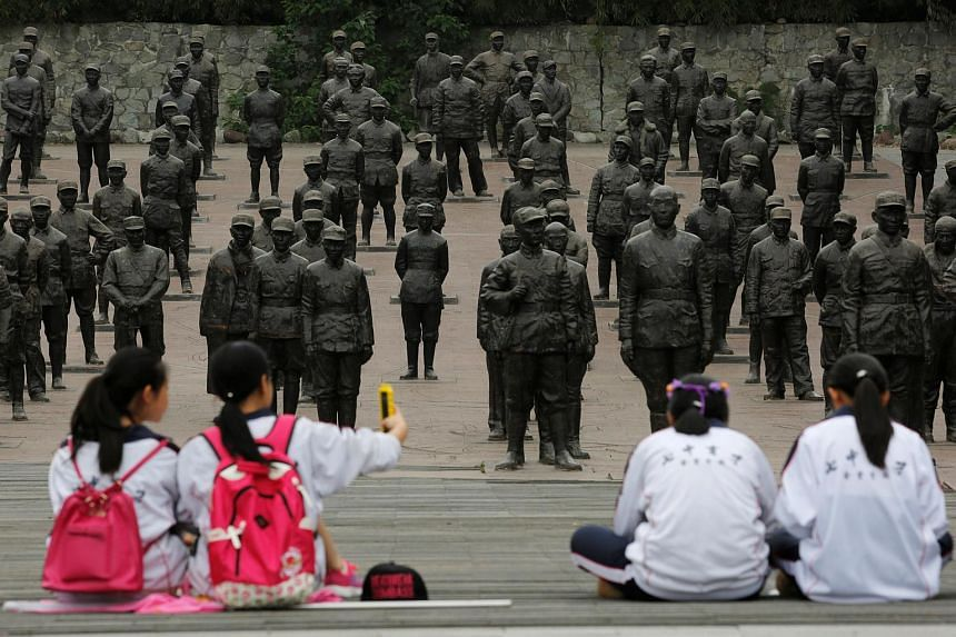 Students sitting at the Chinese Heroes Statues Plaza, which displays war heroes from the War of Resistance against Japan in Anren, Sichuan Province, China, on May 13, 2016.