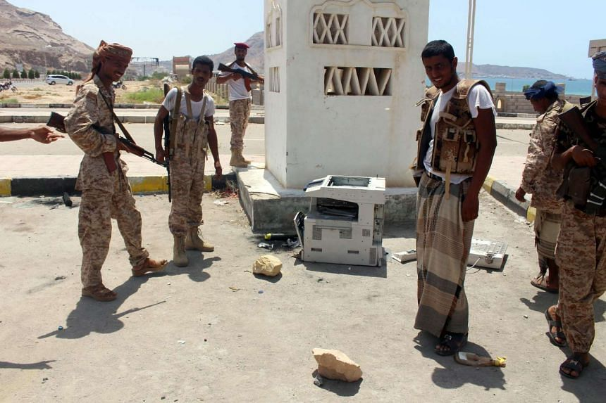 Yemeni soldiers stand next to a photocopier believed was carrying explosives, outside a public security camp following a reported suicide attack in the south-eastern Yemeni port of Mukalla, on May 15, 2016.
