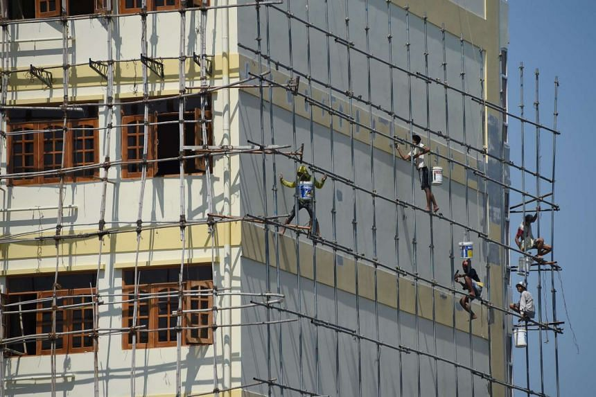 Workers paint a newly constructed apartment building in Yangon, Myanmar, on May 7, 2016.