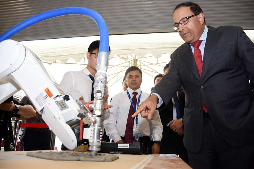 Guest of honour S. Iswaran looking at the new way to 3D print customised advanced concrete structures for buildings.