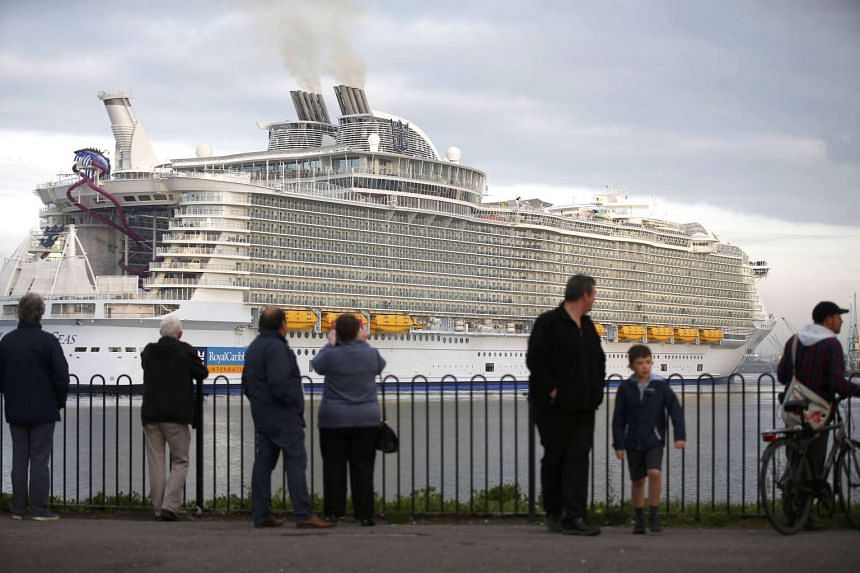 Bystanders watch the world's largest cruise ship, the 362m long Harmony Of The Seas, arrive in port for its maiden voyage in Southampton on May 17, 2016.