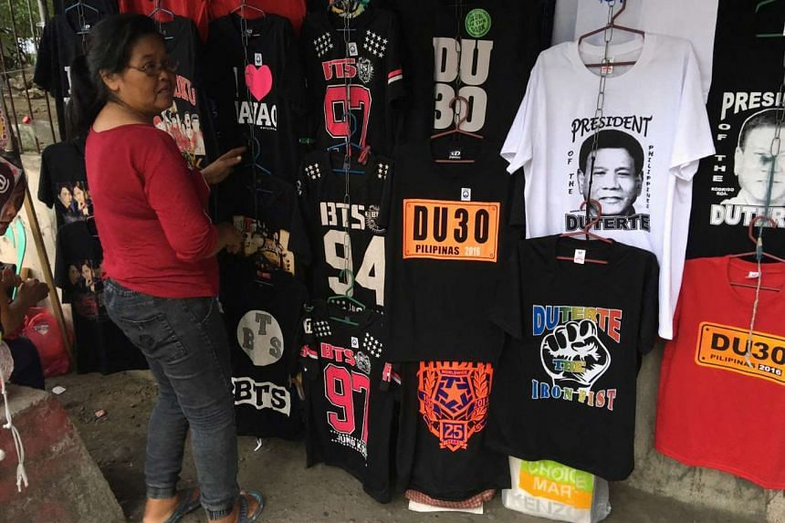 An enterprising vendor displaying souvenir shirts of President-elect Rodrigo Duterte along a sidewalk in Davao city in southern Philippines, on May 16, 2016.