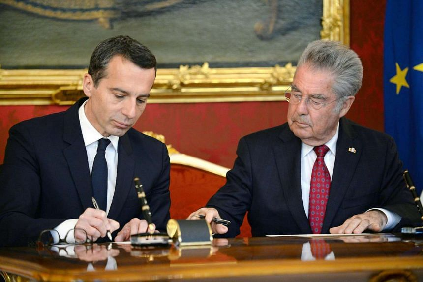 Austria's new chancellor Christian Kern (left) signs the swearing-in documents as chancellor next to President Heinz Fischer at the Hofburg in Vienna, Austria, on May 17, 2016.