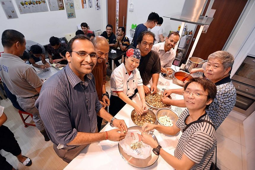 Mr Mathur (left) and some of the 22 other volunteer cooks join chef Geraldine Tan in preparing dinner for 70 children whose mothers are beneficiaries of local charity, Daughters of Tomorrow, which trains and coaches underprivileged women.