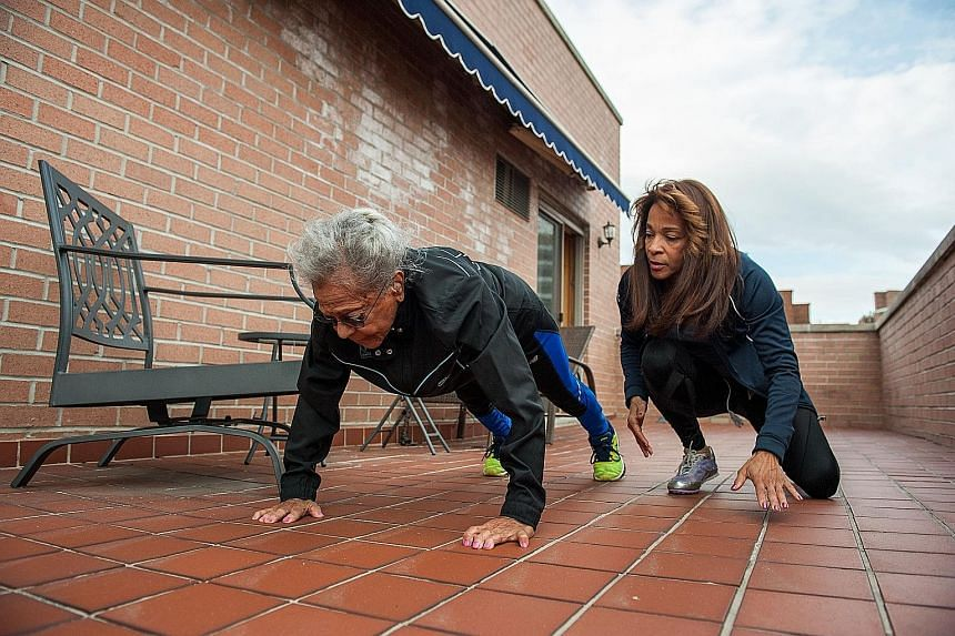 Ms Shelley Keeling watching her mother, Ms Ida Keeling, doing push-ups. To maintain her health, the centenarian follows a stringent regimen of diet and exercise.
