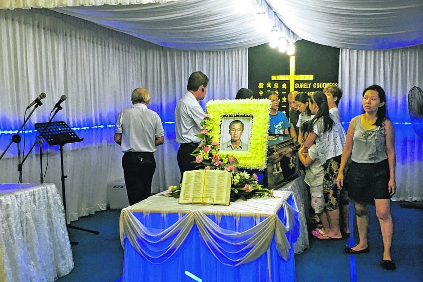 Family members of Mr Lim, 77, at his wake yesterday. Two residents with him when he fell backwards on his mobility scooter took a picture of the lift (right), which was not level with the ground.
