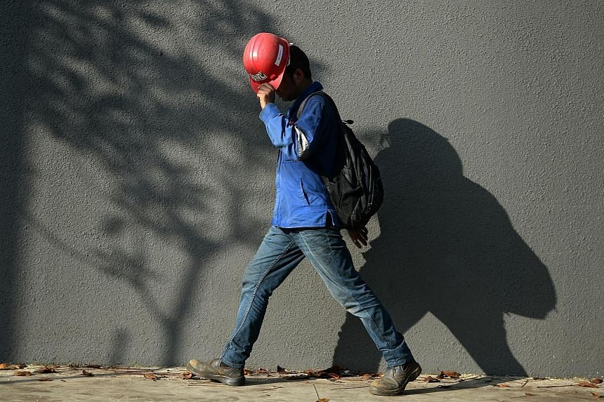 A worker using his helmet to shield himself from the sun. Last month was the hottest April in Singapore since 1929, says Meteorological Service Singapore.