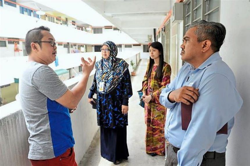 Resident Michael Jin (left) speaking to Welfare Department officers outside his flat in Paya Terubong.