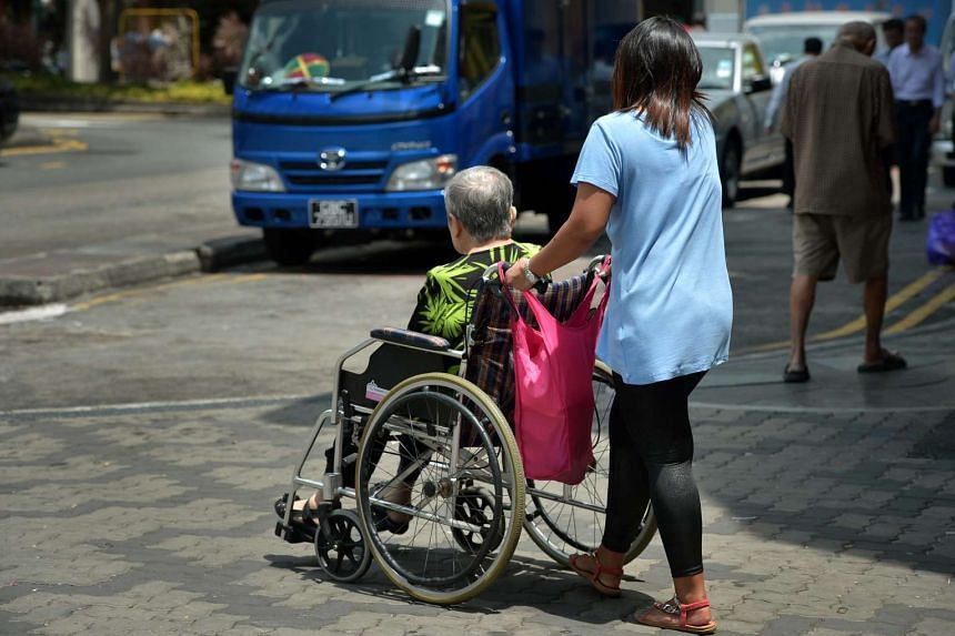 An elderly lady being pushed in a wheelchair by her domestic helper in Chinatown.