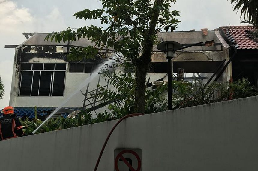 An SCDF officer using a water jet to reduce the remaining smoke, as seen from condominium Shelford Regency.