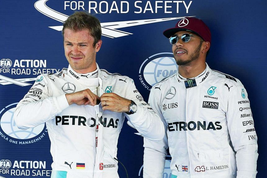 British Formula One driver Lewis Hamilton (right) of Mercedes AMG GP is flanked by his German teammate Nico Rosberg (left) after the qualifying session at the Barcelona-Catalunya circuit in Montmelo, Barcelona, Spain, May 14, 2016.
