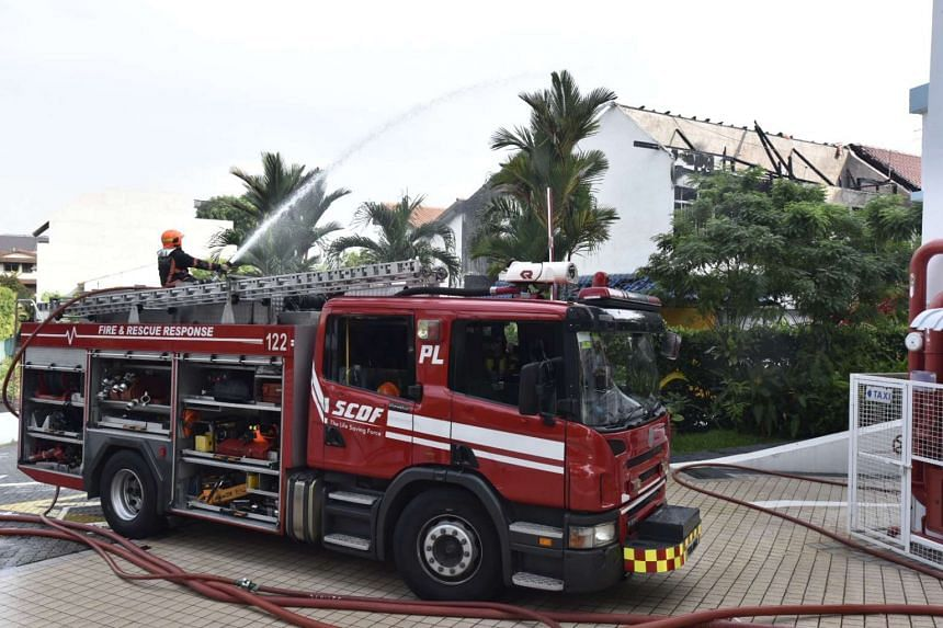 A SCDF fire truck hosing down the pre-school building.