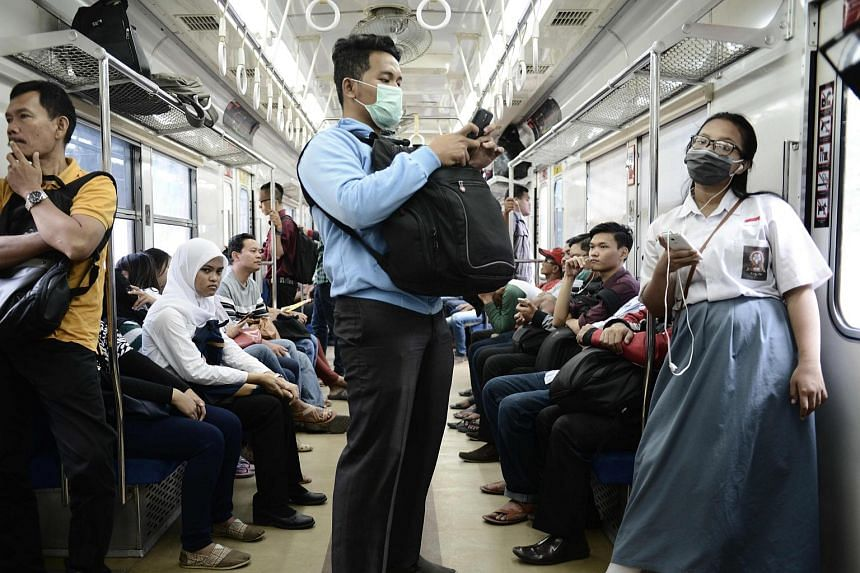 A man and a student wearing masks on a train in Jakarta. Wearing masks has become increasingly popular as residents commmute in the Indonesian capital.