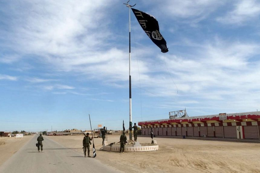 Iraqi security forces lowering an Islamic State flag, west of Ramadi, on March 9.
