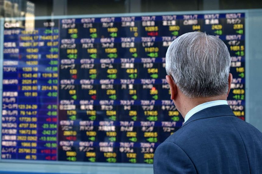 A man looking at a quotation board flashing the Nikkei key index from the Tokyo Stock Exchange in Tokyo on May 13, 2016.