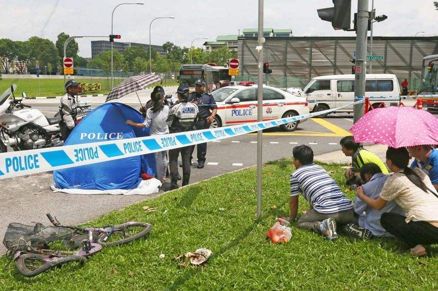 Relatives of Madam Lin Shui Yu (right) sobbing next to the body of the 59-year-old cyclist.