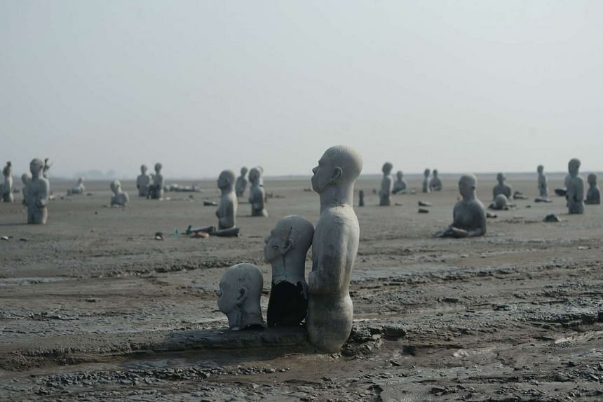 Statues standing semi-submerged in mud, a symbol of the human toll of the 2006 disaster, at a mud volcano area in Sidoarjo, East Java, on March 28, 2016.