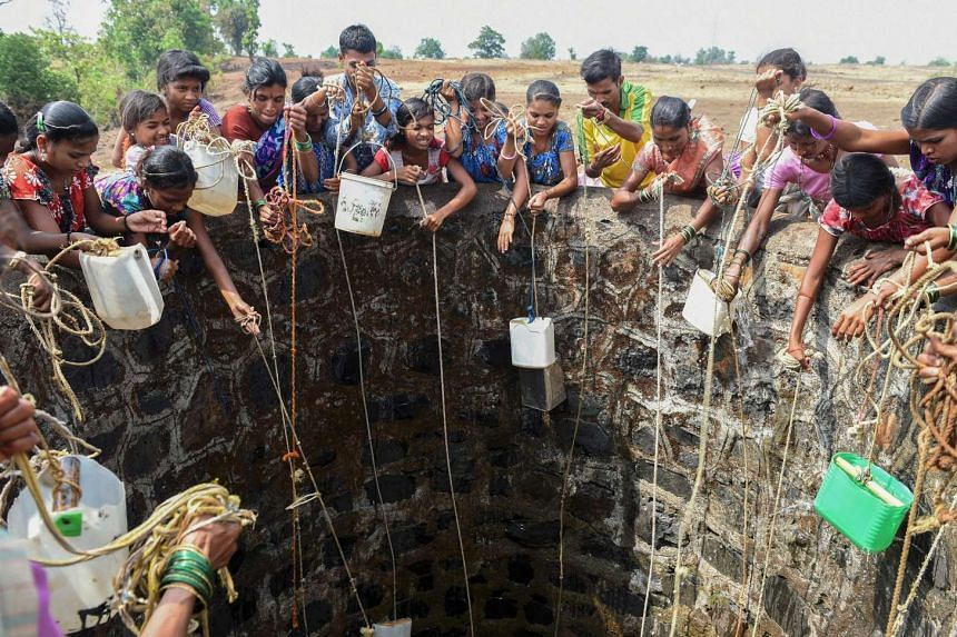 Indian villagers throw containers attached to ropes into a well to collect their daily supply of potable water at Shahapur, on May 13, 2016.