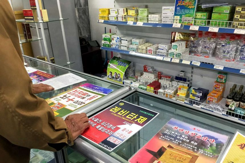 A man looks at advertising posters describing pharmaceuticals in a shop in Pyongyang, North Korea, on May 4, 2016.