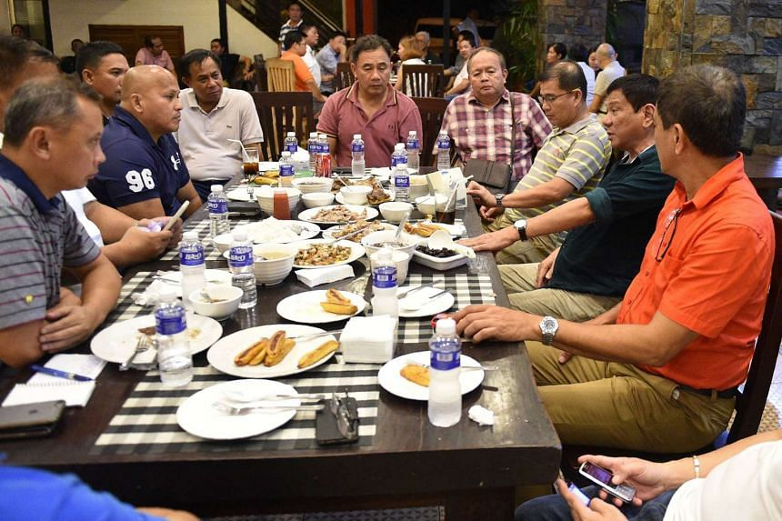 Philippines' president-elect Rodrigo Duterte (second from right) talking with military and police officials at a hotel in Davao City, on May 15, 2016.