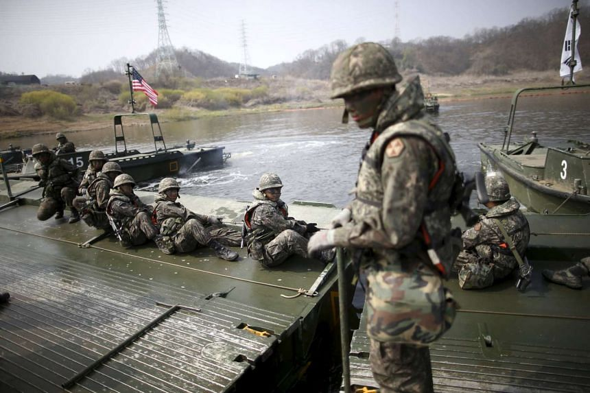 South Korean army soldiers assemble pontoon bridges during a US-South Korea joint river-crossing exercise near a demilitarised zone in Yeoncheon, on April 8, 2016.