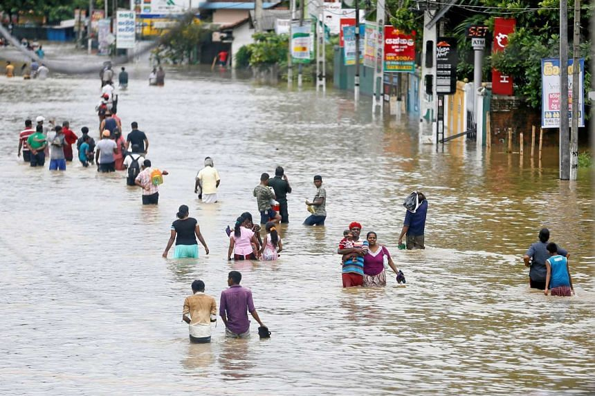 People walk through a flooded road after they moved out from their houses in Biyagama, Sri Lanka, on May 17, 2016.