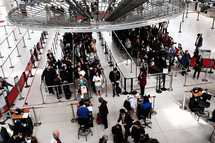 People wait in a security line at John F. Kennedy Airport (JFK) on March 24, 2016 in New York City.