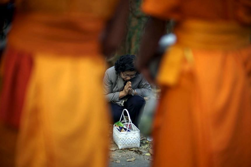 A woman pays her respects to buddhist monks in northern Thailand.