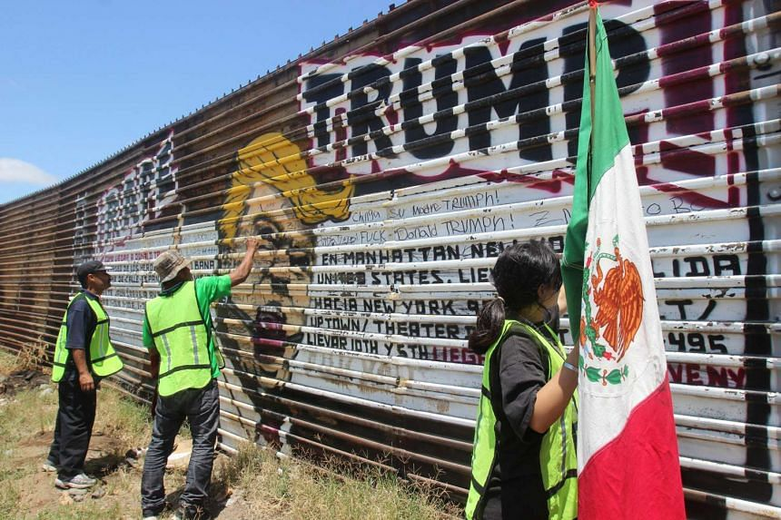 Mexican nationals deported from the US protesting by drawing graffiti over an image of Republican presidential candidate Donald Trump on a section of the border fence between Mexico and the US.